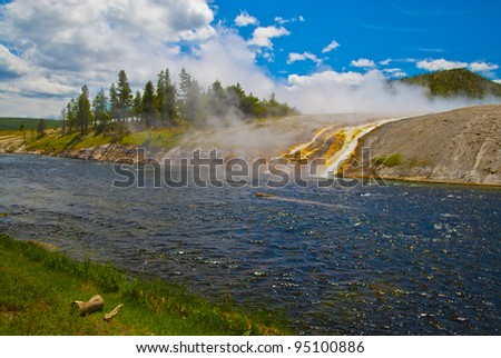 Grand Prismatic Geyser flowing into the Firehole River - stock photo