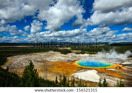Grand Prismatic Pool at Yellowstone National Park with blue sky and puffy clouds - stock photo