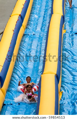 GRAND RAPIDS, MI- AUG 21: Unidentified children from the Grand Rapids area ride the 500-foot inflatable water slide at Lyon street hill on Aug 21, 2010 in Grand Rapids, MI.