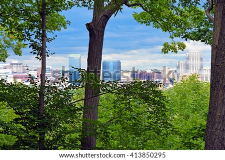 Grand Rapids, Michigan city skyline viewed through green summer foliage on trees