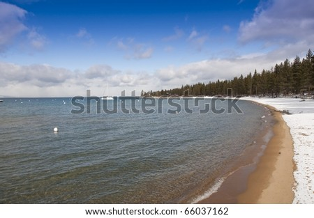 Grand shores of the clear lake Tahoe in winter with snow on the beach - stock photo