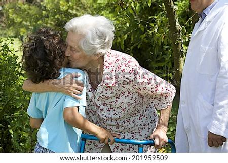 grand son embracing grandmother at hospital park - stock photo
