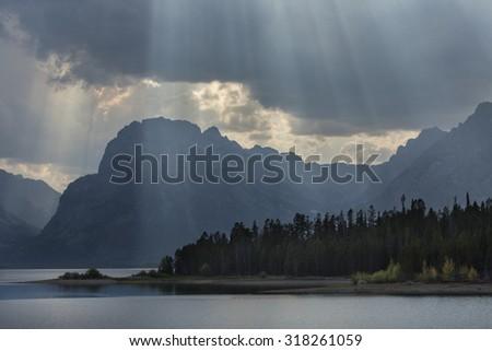 Grand Teton Mountains with curtain of sun rays over Jackson Lake, with pine forest on shoreline, Jackson Hole, Wyoming, horizontal. - stock photo