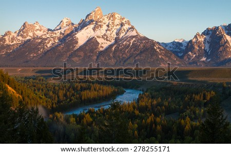 grand teton with the snake river flowing in the foreground through a forest at sunrise. - stock photo