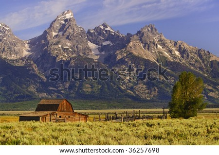 Grand Tetons mountains with barn and fence in foreground - stock photo
