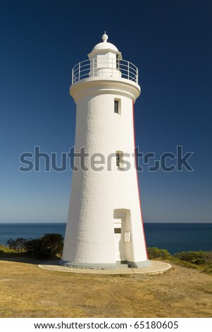 Grand white washed lighthouse looks over the deep blue ocean