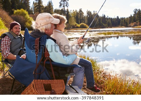 Grandad teaches his grandson to fish at a lake, dad watching - stock photo