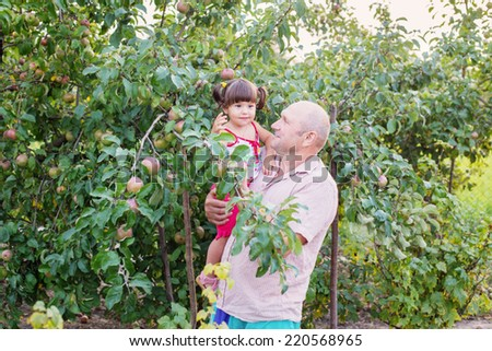 Grandchild and grandfather in garden - stock photo