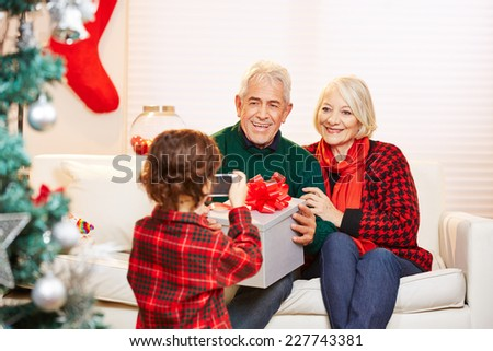 Grandchild taking photo of grandparents with smartphone at christmas - stock photo