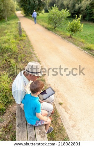 Grandchild teaching to his grandfather to use a electronic tablet on a park bench. Generation values concept. - stock photo