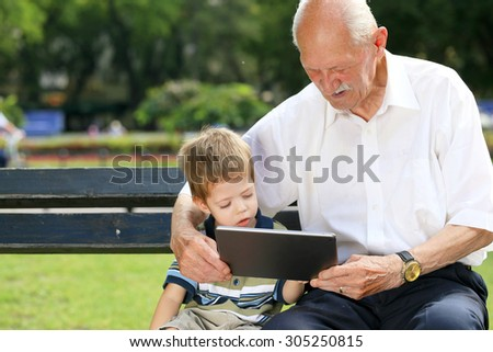 Grandchild teaching to his grandfather to use tablet on a bench - stock photo