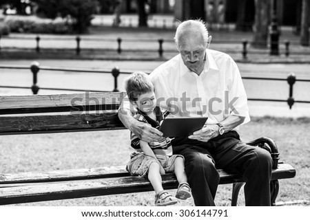 Grandchild teaching to his grandfather to use tablet on a bench. Black and white photography - stock photo
