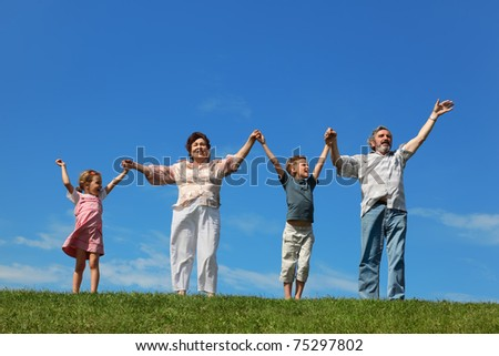 grandchildren and their grandparents standing on lawn and holding for reared hands