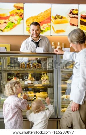 Grandchildren asking grandmother for cakes at cafe dessert appetite restaurant - stock photo