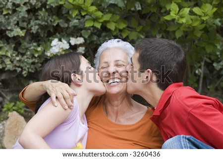 Grandchildren kissing their grandma in the garden - stock photo