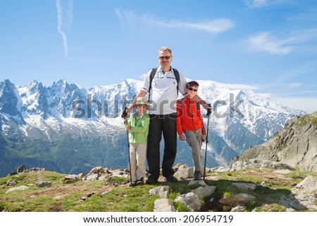 grandchildren with active grandfather in the mountains - stock photo