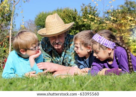 grandchildren with grandparents in the village, on the grass reading a book - stock photo