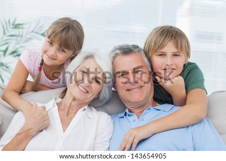 Grandchildren with their grandparents in living room - stock photo