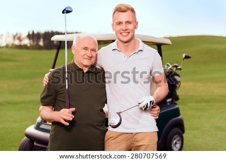 Granddad and grandson. Portrait of two smiling golfers holding golf clubs on background of cart on course. - stock photo