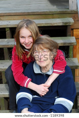 Granddaughter and grandmother on the deck stairs - stock photo