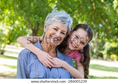 granddaughter and grandmother smiling in a park on a sunny day - stock photo