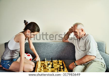 granddaughter and grandpa playing chess front view horizontal - stock photo