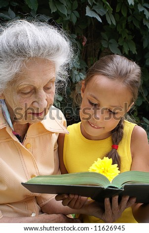 Granddaughter and her grandmother together reading a book - stock photo