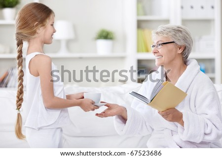 Granddaughter brought a cup of tea grandmother - stock photo