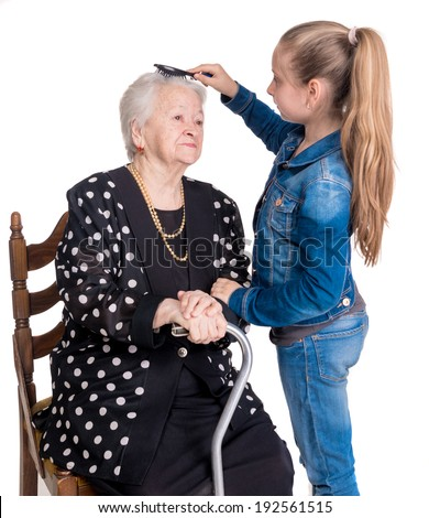 Granddaughter combing hair her grandmother on a white background
