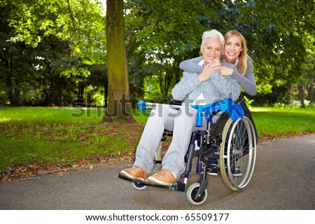 Granddaughter embracing her grandmother in wheelchair outdoors - stock photo