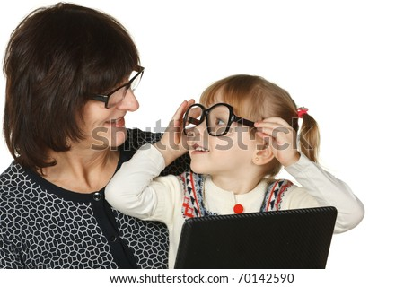 Granddaughter fooling with grandmother'Â?Â?s glasses isolated on white - stock photo