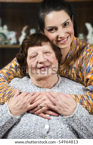 Granddaughter giving a hug to her grandma and both smiling and holding their hands together - stock photo