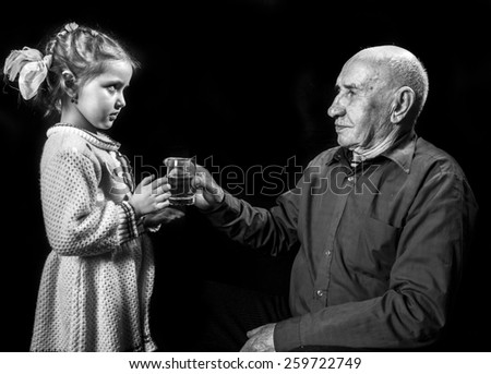 granddaughter grandfather gives a glass of water - stock photo