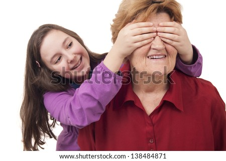 Granddaughter hands over grandmother eyes close up Isolated