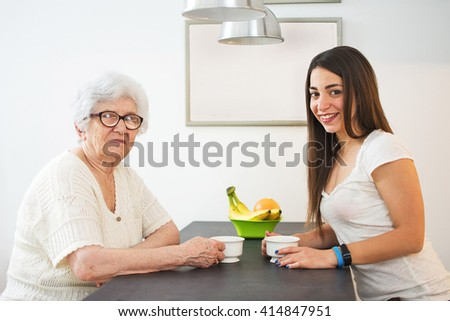 Granddaughter having a cup of tea with her grandmother at home. - stock photo