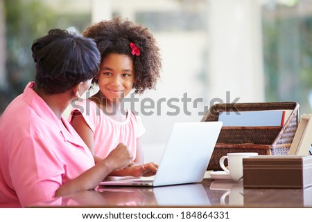 Granddaughter Helping Grandmother With Laptop - stock photo