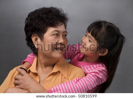 granddaughter hugging grandmother and looking at each other - stock photo