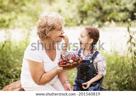 granddaughter is feeding her grandmother with cherries in the garden - stock photo