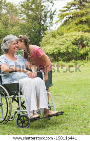 Granddaughter kissing cheek of grandmother in wheelchair outside in the park