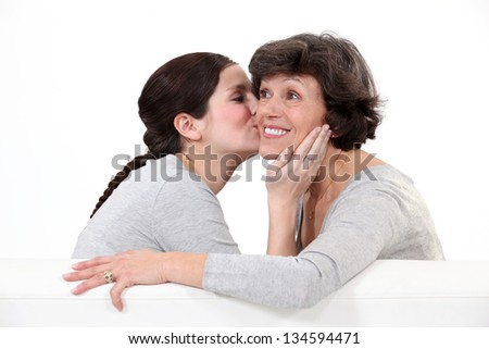 Granddaughter kissing grandmother - stock photo