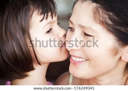 Granddaughter kissing grandmother - stock photo