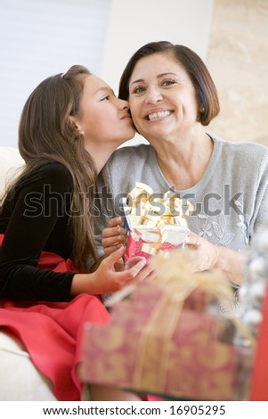 Granddaughter Kissing Grandmother On The Cheek,And Giving Her A Christmas Gift - stock photo