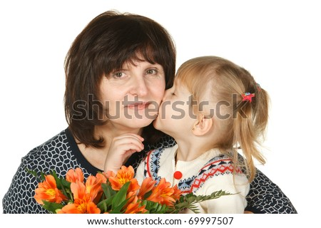 Granddaughter kissing her grandmother with closed eyes having bunch of flowers; isolated on white - stock photo