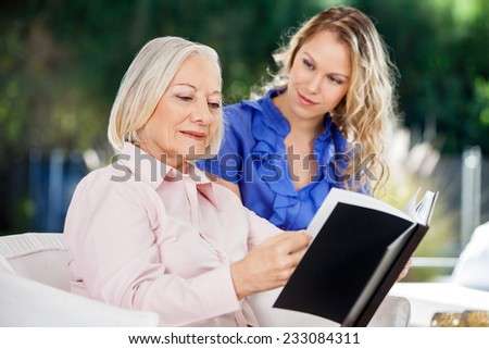 Granddaughter looking at grandmother reading book on nursing home porch - stock photo