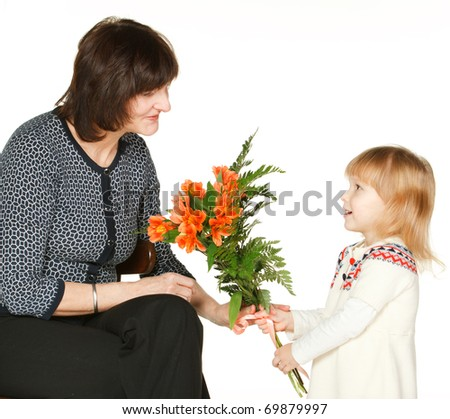 Granddaughter offering bunch of flowers to her grandmother, isolated on white - stock photo