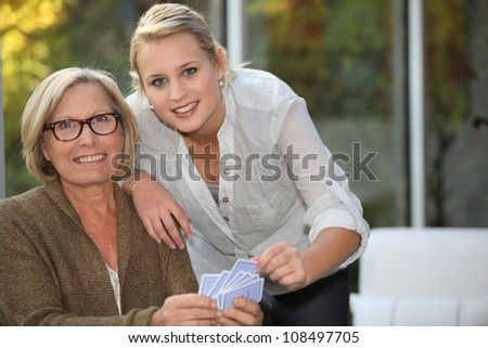 Granddaughter playing cards with Grandma - stock photo