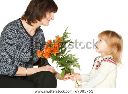 Granddaughter presenting bunch of flowers to her grandmother, isolated on white - stock photo