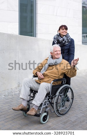 Granddaughter pushing her grandpa in a wheelchair