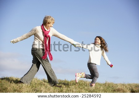 Granddaughter Running And Pulling Grandmother By The Hand - stock photo