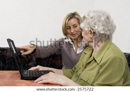 granddaughter shows her grandmother the work on a laptop